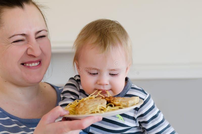 A mãe está alimentando o menino pequeno pela refeição normal da placa fotografia de stock royalty free