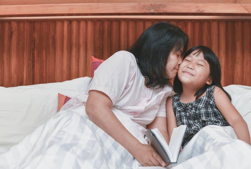 A mãe está beijando sua filha no mordente imagem de stock
