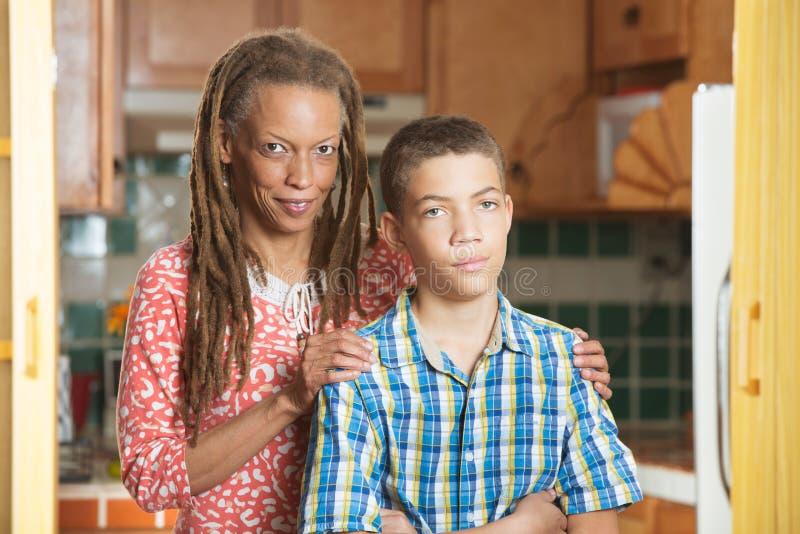 A mãe está com seu filho adolescente com uma mão em um ou outro ombro fotografia de stock royalty free