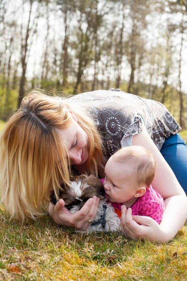 A mãe está jogando com cachorrinho e bebê imagens de stock royalty free