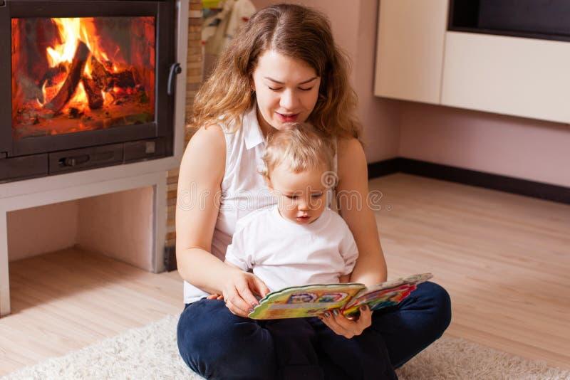 A mãe está lendo para seu filho perto da chaminé foto de stock