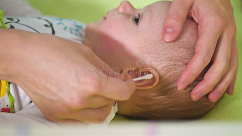 A mãe está limpando suas orelhas do bebê fotografia de stock