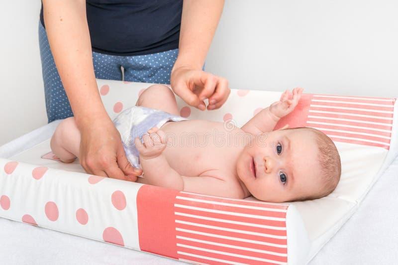 A mãe está mudando o tecido a seu bebê pequeno foto de stock