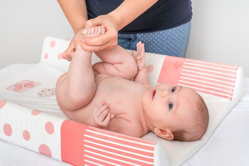 A mãe está mudando o tecido a seu bebê pequeno fotografia de stock royalty free