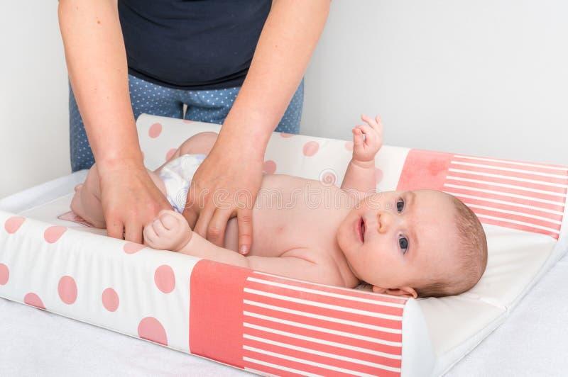 A mãe está mudando o tecido a seu bebê pequeno fotos de stock royalty free