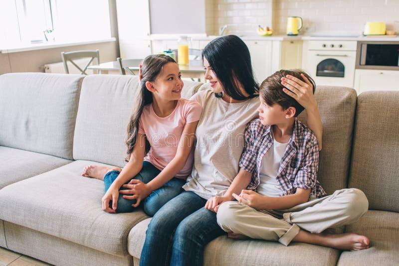 A mãe está sentando-se no sofá com suas crianças Está abraçando-os A mulher olha a filha Guarda a mão na cabeça do ` s do menino foto de stock royalty free