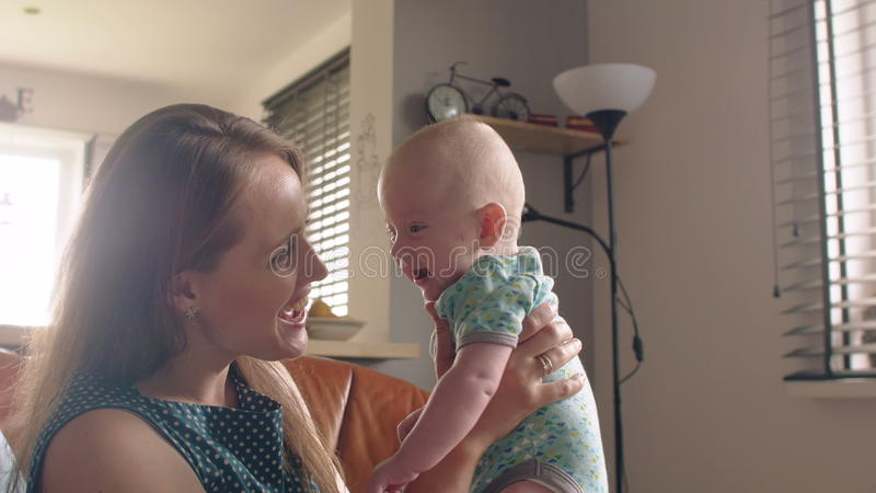 A mãe está sustentando seu bebê de sorriso adorável que senta-se no sofá 4K foto de stock royalty free