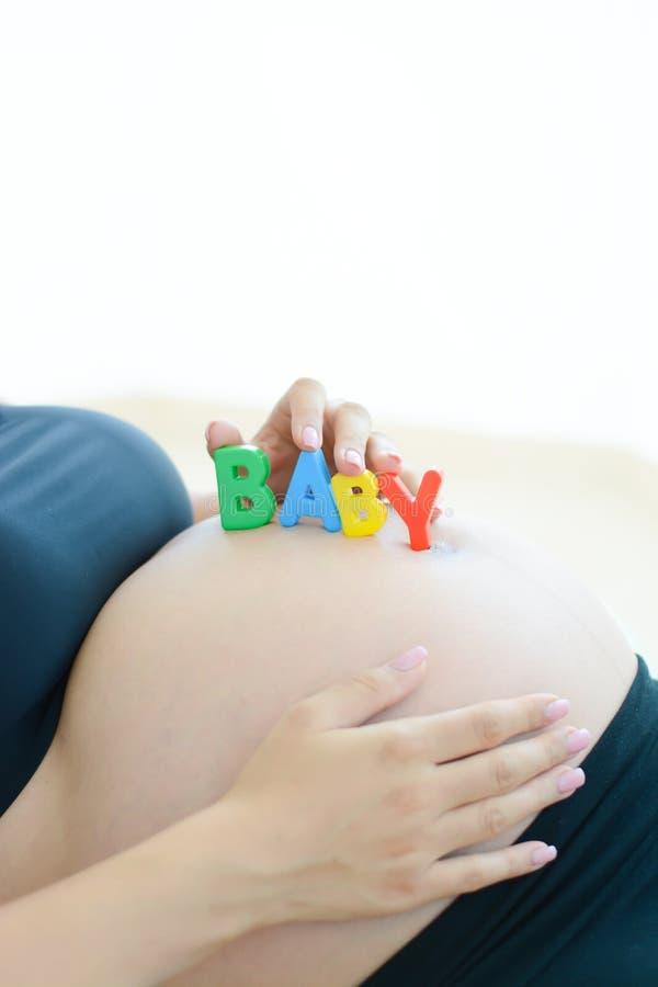 A mãe expectante nova com letra obstrui o bebê da soletração em sua barriga fotografia de stock