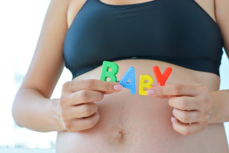 A mãe expectante nova com letra obstrui o bebê da soletração em sua barriga grávida fotos de stock