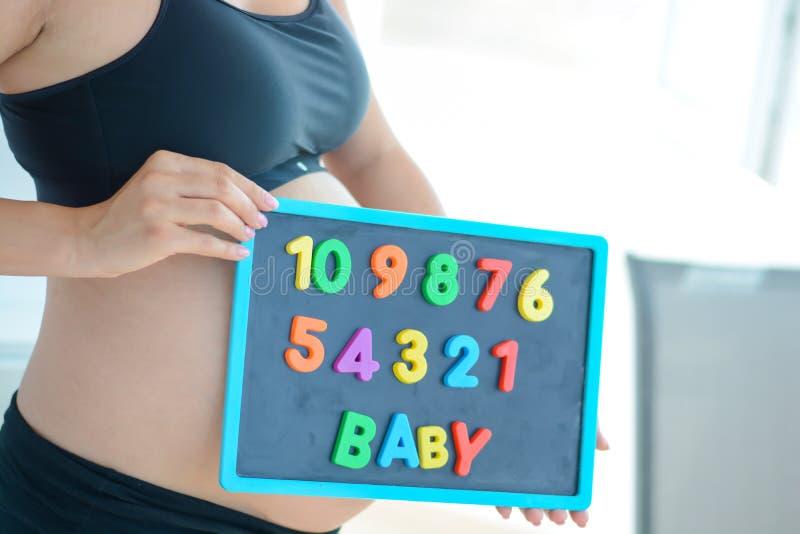 A mãe expectante nova com letra obstrui o bebê da soletração no quadro-negro magnético foto de stock royalty free