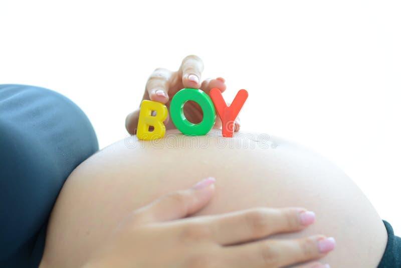 A mãe expectante nova com letra obstrui o menino da soletração em sua barriga grávida fotos de stock royalty free