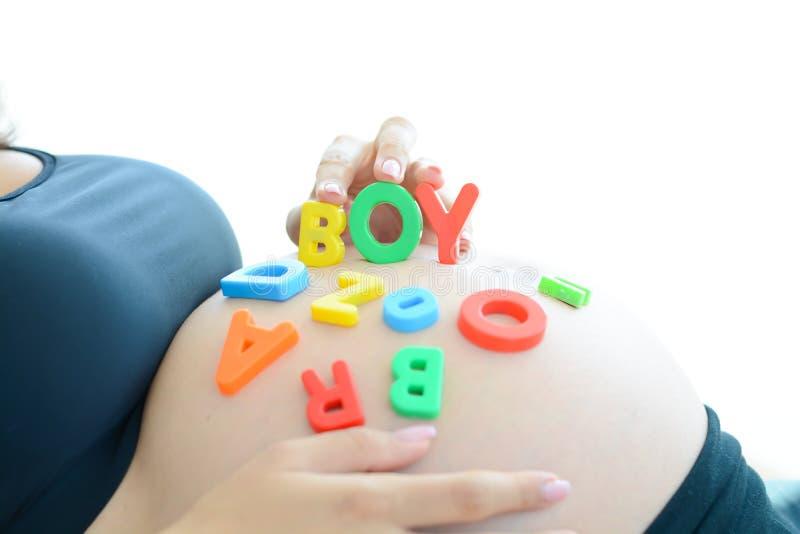 A mãe expectante nova com letra obstrui o menino da soletração em sua barriga grávida foto de stock royalty free