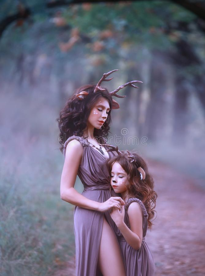 A mãe feericamente de um cervo no trajeto abraça sua criança e guarda sua mão, fechou seus olhos e escuta o som de um enevoado imagens de stock royalty free