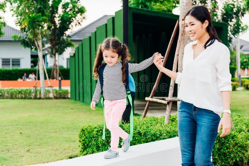 Mãe feliz asiática que guarda as mãos suas crianças da filha fotos de stock