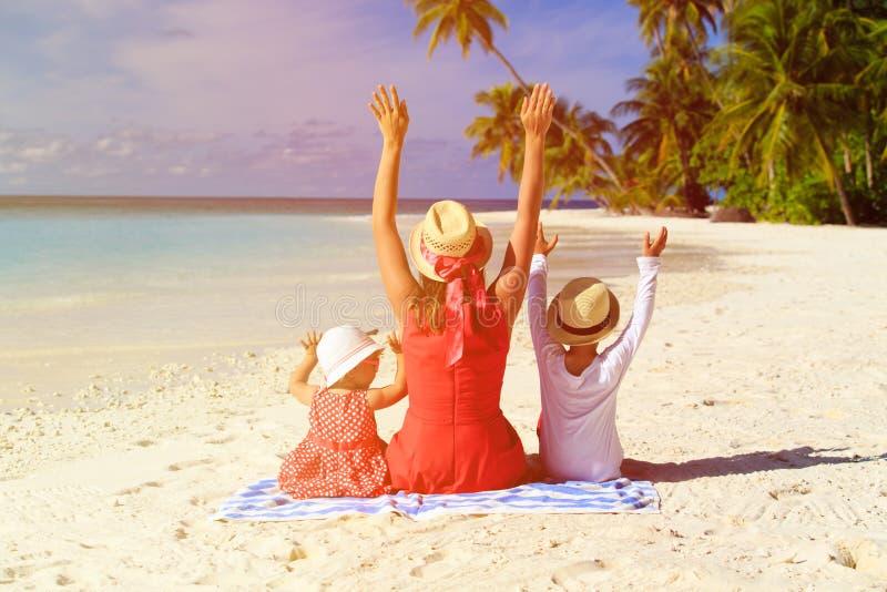 Mãe feliz com as duas crianças na praia fotografia de stock royalty free