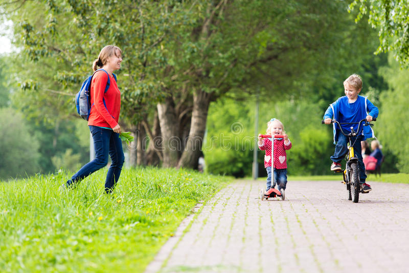 Mãe feliz com as duas crianças no 'trotinette' e na bicicleta dentro fotos de stock royalty free