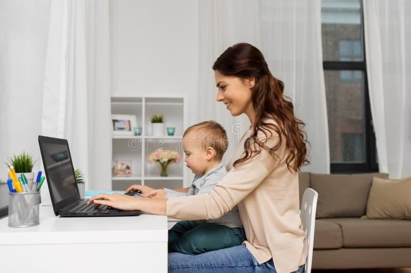 Mãe feliz com bebê e portátil que trabalha em casa imagens de stock royalty free