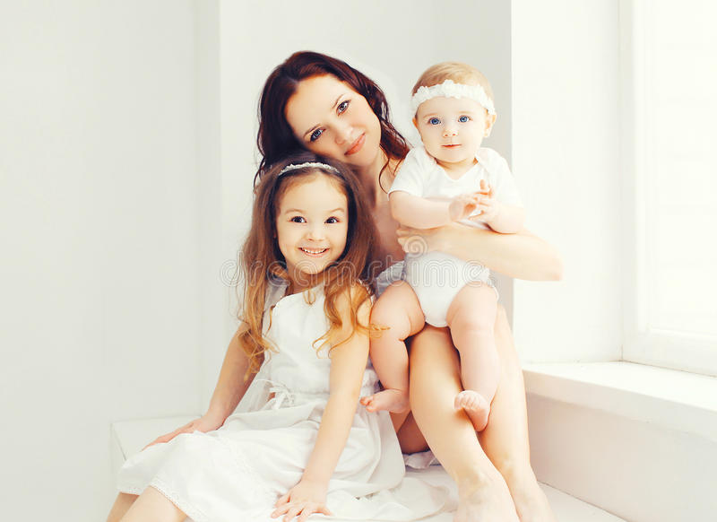 Mãe feliz com dois suas crianças das filhas em casa fotografia de stock royalty free
