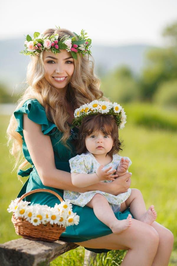 Mãe feliz com a filha pequena no prado fotos de stock