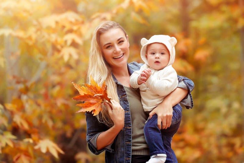 Mãe feliz com o bebê no parque do outono fotografia de stock royalty free