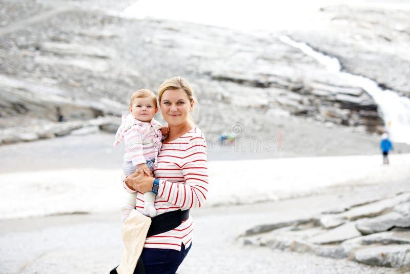 Mãe feliz com o bebê pequeno que viaja na trouxa Caminhando a aventura com a criança nas montanhas imagens de stock