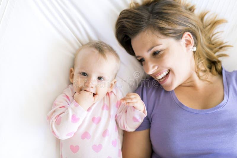 Mãe feliz com o bebê que encontra-se na cama em casa imagens de stock