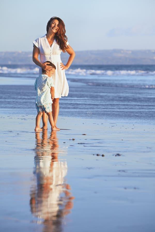 Mãe feliz com o filho que fica na praia lisa do mar imagens de stock