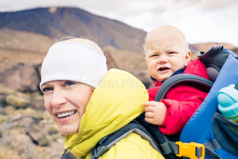 Mãe feliz com o rapaz pequeno que viaja na trouxa fotos de stock