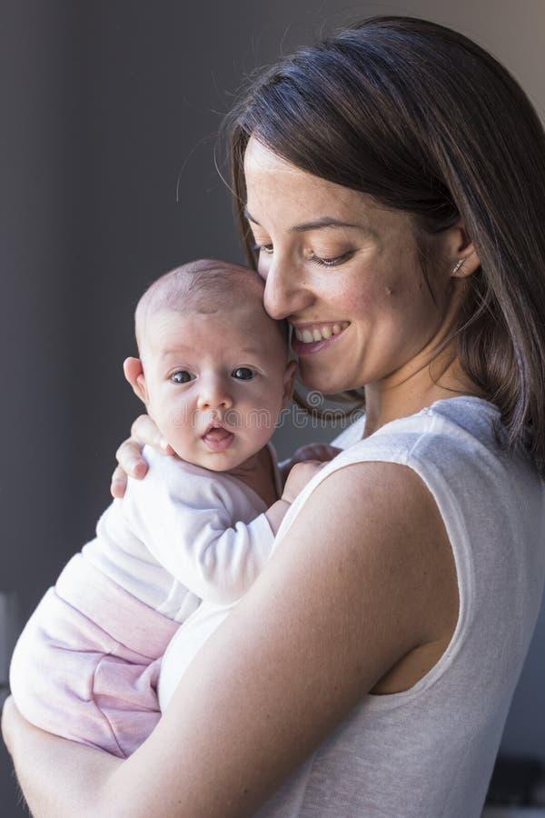 mãe feliz com seu bebê em casa Estilo de vida dentro e conceito do amor da família foto de stock royalty free