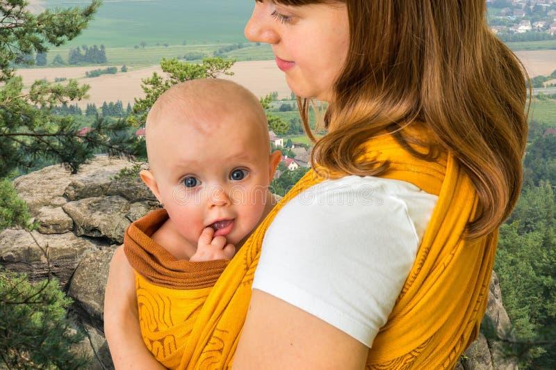 Mãe feliz com seu bebê em um estilingue fotografia de stock royalty free