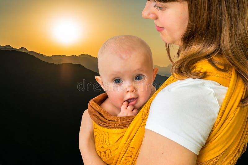 Mãe feliz com seu bebê em um estilingue fotos de stock royalty free