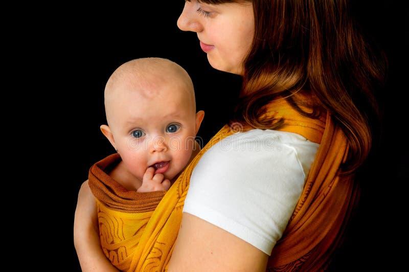 Mãe feliz com seu bebê em um estilingue - isolado sobre para trás imagens de stock