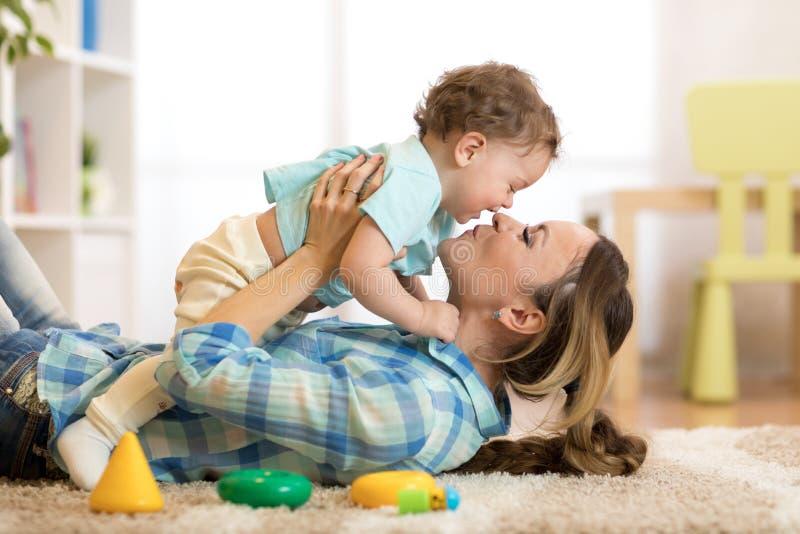 Mãe feliz com seu bebê que tem o passatempo do divertimento no tapete no berçário fotos de stock royalty free