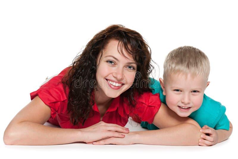Mãe feliz com sua mentira do filho no assoalho foto de stock