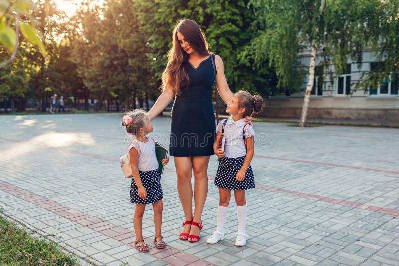 Mãe feliz conhecendo suas filhas depois de aulas fora do ensino primário A família vai para casa De volta à escola fotos de stock royalty free
