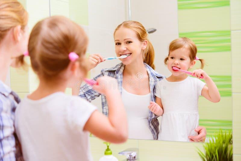 Mãe feliz da família e criança da filha que escova seu toothb dos dentes foto de stock royalty free