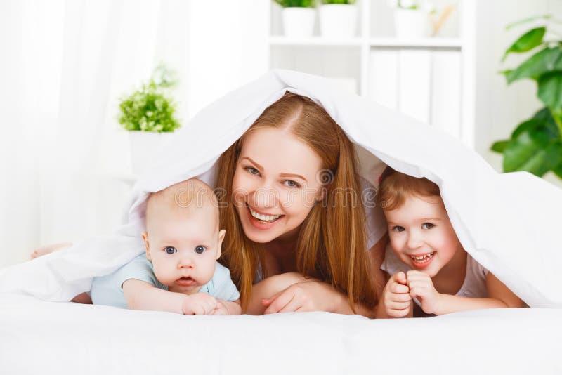 Mãe feliz da família e duas crianças, filho e filha no un da cama imagens de stock royalty free
