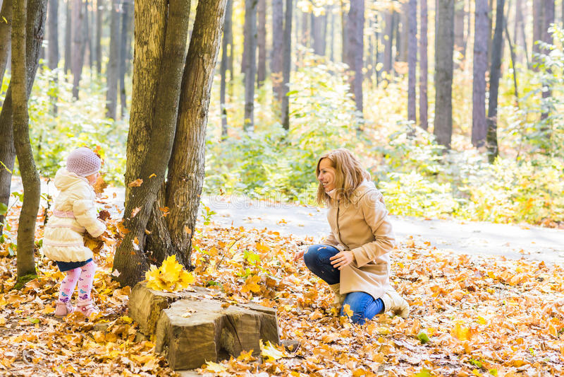 A mãe feliz da família e a menina da criança que joga o lance saem no parque do outono fora fotografia de stock