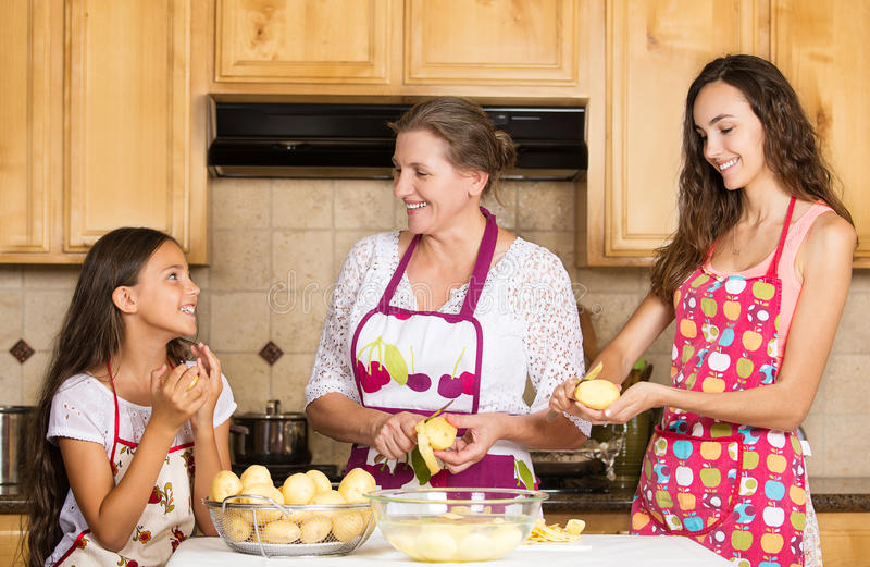 Mãe feliz da família, filha que cozinha o alimento em uma cozinha fotografia de stock