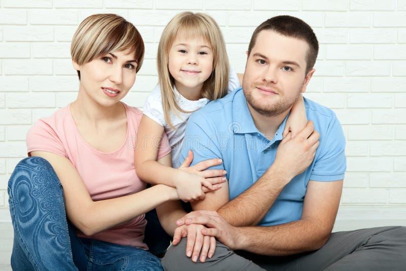 Mãe feliz da família, pai e duas crianças jogando e afagando em casa no assoalho fotos de stock royalty free