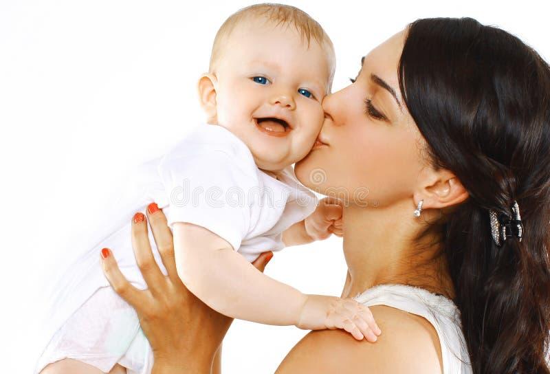 Mãe feliz da família que beija o bebê fotos de stock