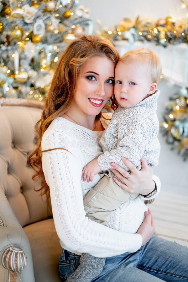 Mãe feliz e bebê pequeno no interior do Natal imagens de stock