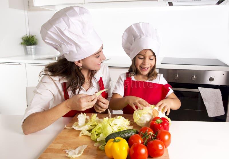 Mãe feliz e cozinha pequena da filha em casa que preparam a salada no chapéu do avental e do cozinheiro foto de stock