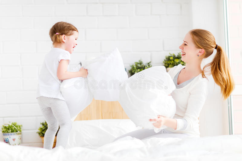 Mãe feliz e criança da família que jogam na luta da cama e de descanso imagem de stock royalty free