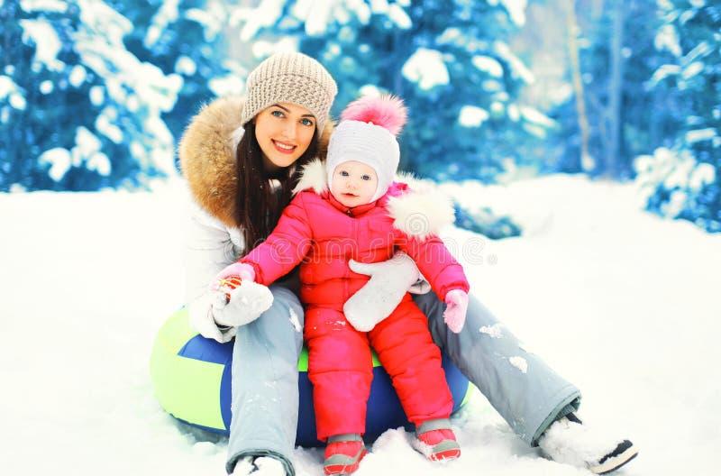 Mãe feliz e criança de sorriso do inverno que sentam-se no trenó no dia nevado fotos de stock