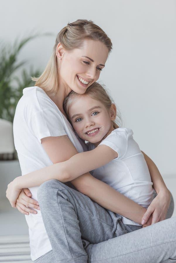 mãe feliz e filha bonitas que abraçam e que olham fotos de stock