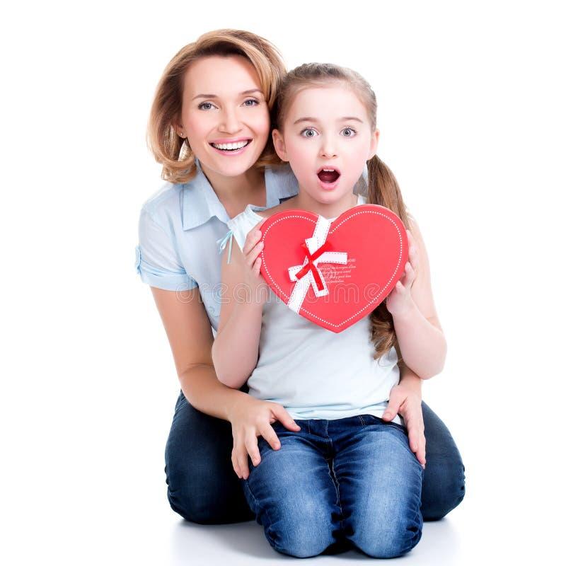 A mãe feliz e a filha nova guardam o presente para o aniversário imagens de stock royalty free