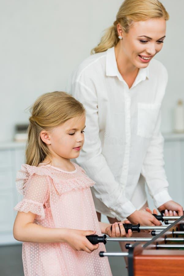 mãe feliz e filha pequena adorável que jogam o futebol da tabela imagem de stock royalty free