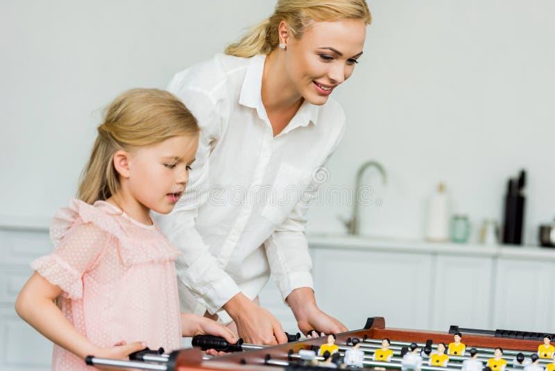 mãe feliz e filha pequena bonito que jogam o futebol da tabela imagens de stock