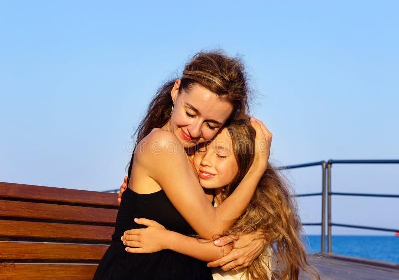 A mãe feliz e a filha pequena estão abraçando no por do sol imagens de stock